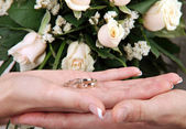 Wedding rings in hand on the background of bunch of roses — Stock Photo