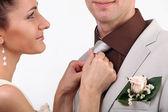 Bride adjusting groom's tie on white background — Stock Photo
