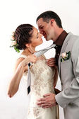 Bride pulling groom by his tie for a kiss — Stock Photo