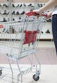 Woman pushing shopping cart in shoe store, close-up — Stock Photo