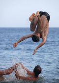 Male friends playing in the sea, one performing somersault — Stock Photo