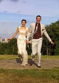 Appena si sposa felice coppia in esecuzione nel parco — Foto Stock