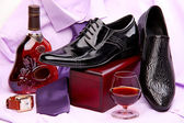 Set of male shoes, bottle and glass of brandy, and male wristwatch placed on a violet shirt with a tie — Stock Photo