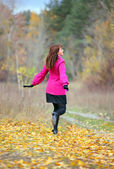 Woman in the pink coat running in the park — Stock Photo
