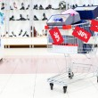 Shopping cart full of shoe boxes in a shoe department with added images of discount tags — Stock Photo