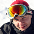 Close-up portrait of snowboarder sitting on snow — Stock Photo