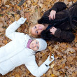 Two female friends lying down in autumn leaves — Stock Photo #4769133