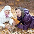 Happy couple lying down in autumn leaves in the park — Stock Photo