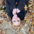 Beautiful young woman lying down in autumn foliage, view from above — Stock Photo