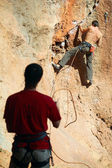 Two rock climbers, one belaying — Stock Photo