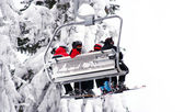 Skiers on a ski-lift. One skier waving his hand. — Stock Photo