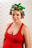 Pretty pregnant woman with hair rollers — Stock Photo