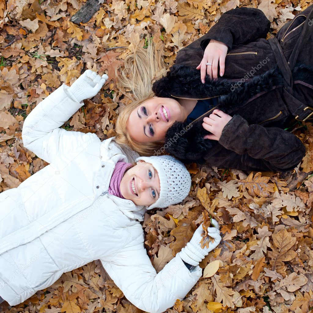 Two female friends lying down in autumn leaves   Stock Photo #4769133