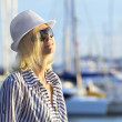 Young woman is standing at the yacht berth, enjoying the sunrise — Stock Photo