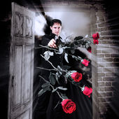 Man killer with gun and red roses — Stock Photo