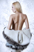 Sexy blonde woman in fur coat back — Stock Photo