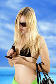 Sexual girl on beach with moble phone — Stock Photo