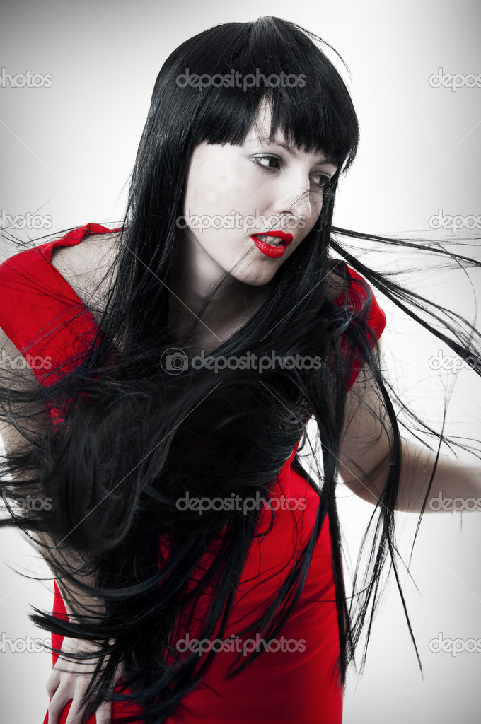 Fashion portrait of fresh and beautiful young brunet woman with red evening dress and hair developing on a wind. Flying healthy long black hair — Stock Photo #4822155