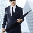 Successful sexual business man with umbrella — Stock Photo #5043814