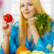 Royalty-Free Stock Photo: Blonde woman on light kitchen at home with vegetables