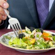 Stock Photo: Man eating salad. Hand with fork closeup