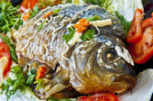 Fried fish with fresh herbs, tomatoes — Stock Photo