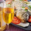Fried fish with vegetables. And white wine in glass — Stock Photo