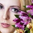 Female face with perfect skin and flowers — Stock Photo