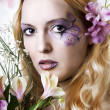 Young woman with makeup and exotic flowers — Stock Photo