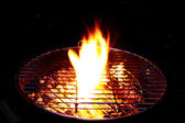 Bright fire flames on barbecue on black background — Stock Photo