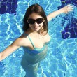 Sexual girl is swimming in blue swimming pool — Stock Photo