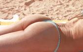 Bronzlaşmış bikini kız g-string kıçı güneşlenme — Stok fotoğraf