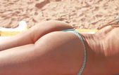Trasero bronceada bikini tanga de una chica tomando el sol — Foto de Stock