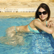 Sexual girl in bikini is relaxing in blue jacuzzi in glasses — Stock Photo
