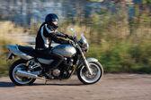 Adam yolda bir motosiklet sürme — Stok fotoğraf