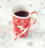 Tea in christmas cup and striped candy — Stock Photo