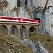 Train on an old bridge is going into a tunnel in mountains - Stock Photo