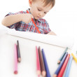 A little boy at the table draws with colored pencils — Stock Photo #5303364