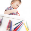 A little boy at the table draws with colored pencils — Stock Photo