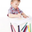 A little boy at the table draws with colored pencils — Stock Photo #5303386