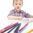 A little boy at the table draws with colored pencils — 图库照片