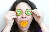 Woman holds two slices of kiwi before her eyes — Stock Photo