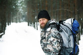 Traveller with backpack in winter forest — Stock Photo