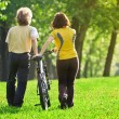 Young couple in the park with a bycicle — Stock Photo