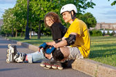 Young couple put on inline skates — Stock Photo