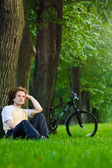 Young man siting in the park under the tree near his bycicle — Stock Photo
