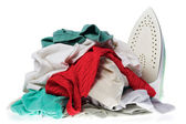 Iron and disorderly heap clothes — Stock Photo
