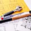 Stock Photo: Tools on house plans including hammer, screw driver and monkey wrench