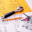 Stock Photo: Tools on house plans including pencil, keys and monkey wrench.