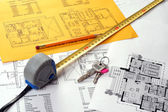 Tools on house plans including measuring tape, keys and pencil — Stock Photo